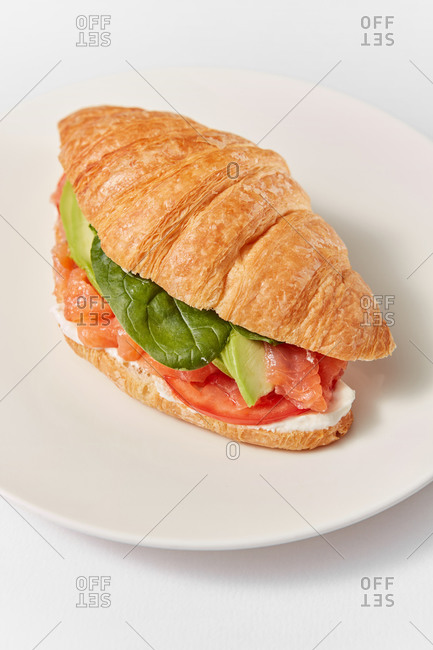 Close up view of freshly cooked homemade croissant sandwich with natural salmon fish, avocado, green leaf and ripe tomatoes on a ceramic plate on a white background, copy space.