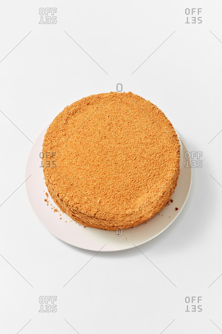 Top view of freshly baked homemade sweet honey cake on a ceramic plate on a white background, copy space. Top view.