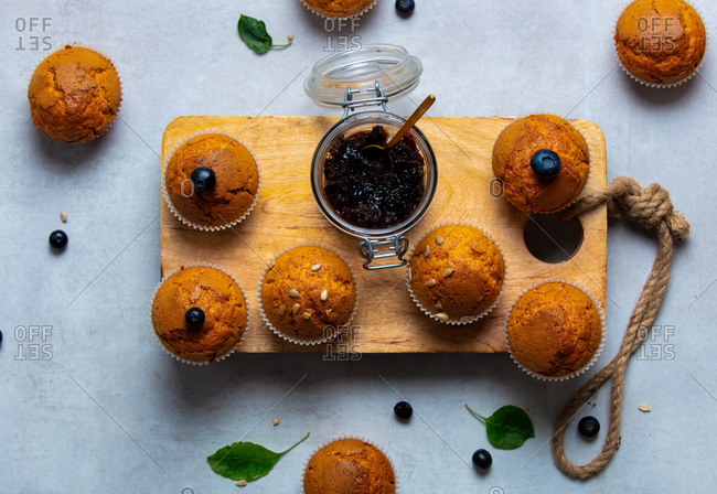 Cupcakes with blueberries and jam on table, above view.