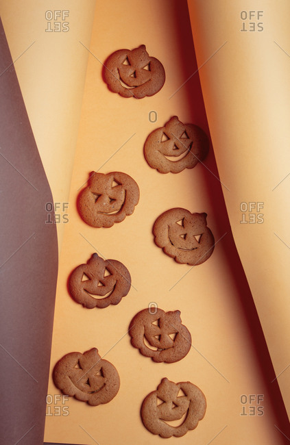Pumpking halloween cookies in brown and yellow background