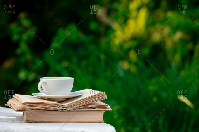 White cup of coffee and books on wooden background in a garden