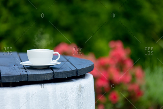 White cup of coffee on a old wooden table in a garden
