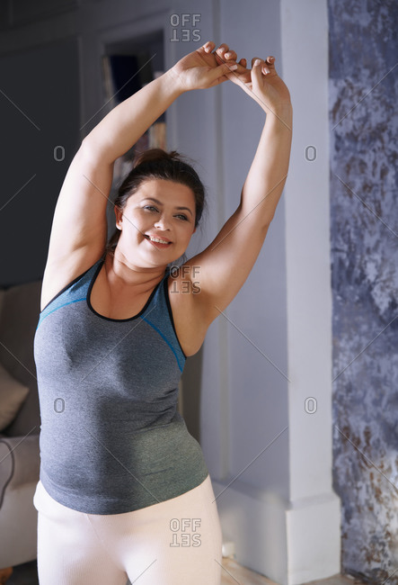 Plus size woman doing sports exercise at home