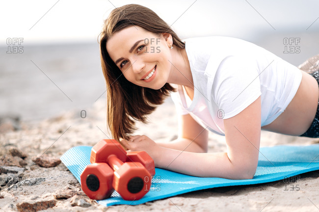 Fitness outdoors. Young attractive girl in sportswear is engaged fitness on the nature near the sea on a mat, she doing plank exercise