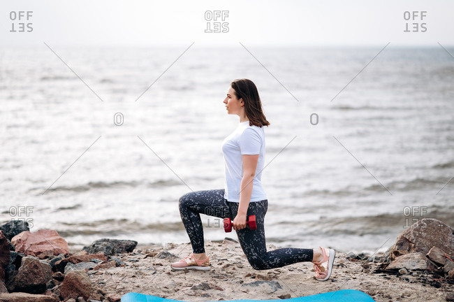 Workout on a beach. Attractive young woman in sportswear doing fitness exercising, she does squats near the sea with dumbbells