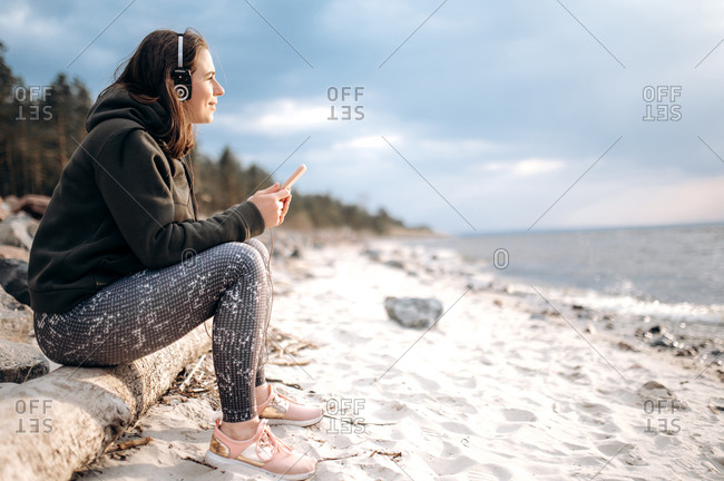 Chillout time outdoors. Calm attractive young woman listening to music with headphones while sitting on the beach by the sea
