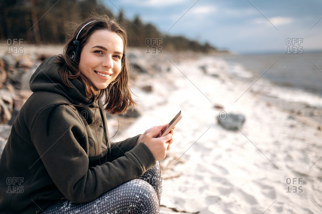 Chillout time. Smiling charismatic girl listening to music with headphones while sitting on the beach by the sea in a relaxed mood