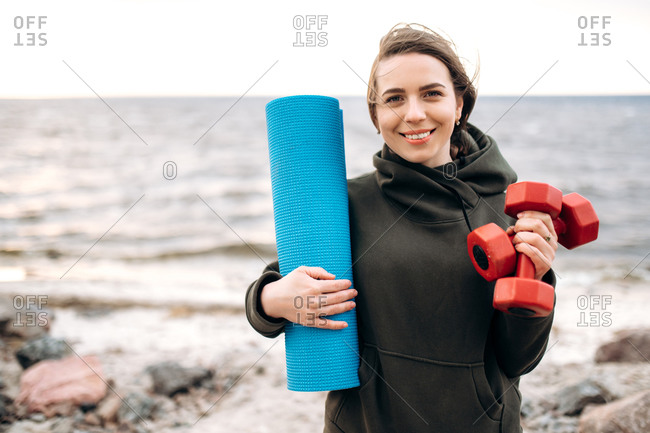 Attractive smiling caucasian girl holds dumbbells and a sports mat in her hands before fitness workout outdoor