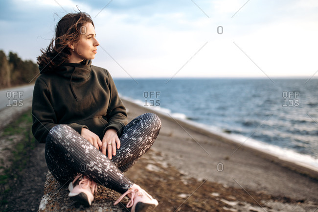 Attractive alone young girl in sportswear and in a relaxed calm mood sits near the sea and looks at the sunset