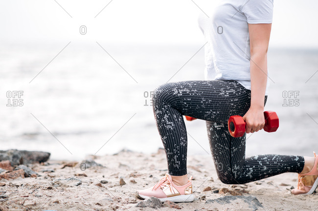 Fitness training outdoor. Female legs and dumbbells close-up. A girl doing squats with dumbbells during outdoors workout