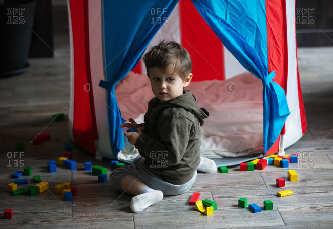 Toddler boy play with blocks in a little house indoor