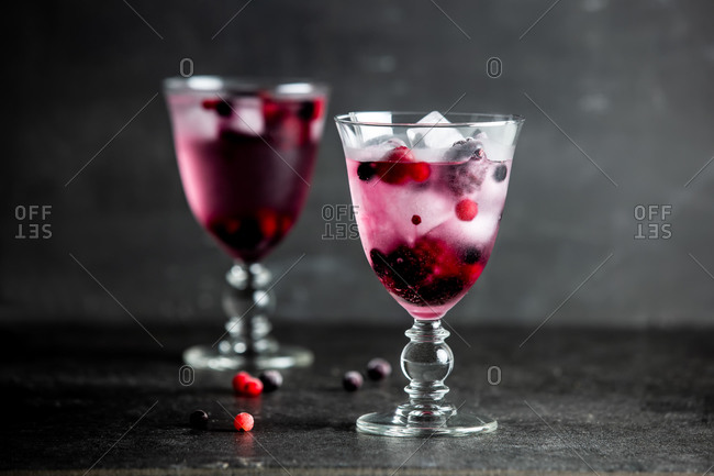 Drink with blackberries, raspberries and cranberries in glasses on a table