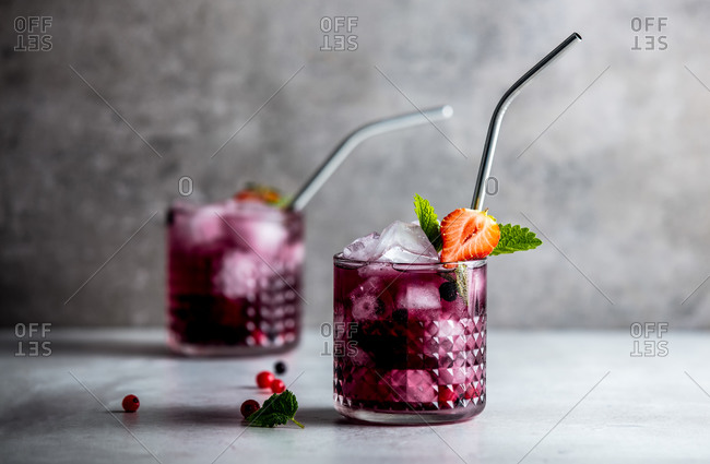 Drink with strawberry, blackberries, raspberries and cranberries in glasses on a table