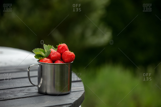 strawberry in a metal mug on a table