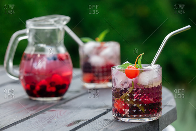 Drink with cherry, blackberries, raspberries and cranberries in glasses on a table