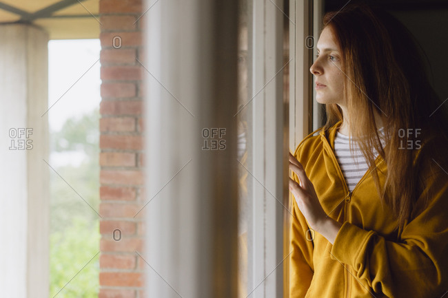 Pensive redheaded woman looking out of window