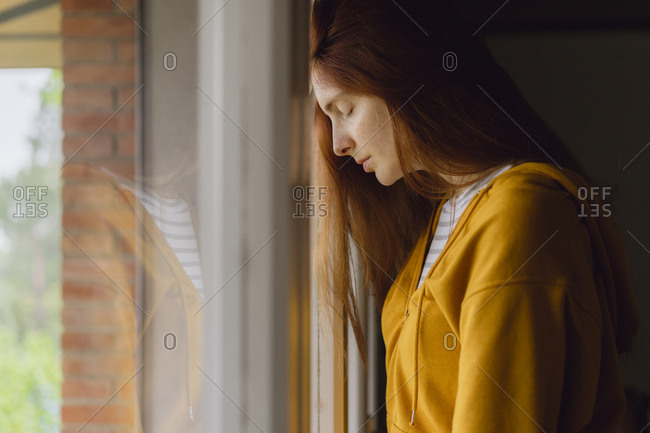 Redheaded woman with eyes closed leaning against window