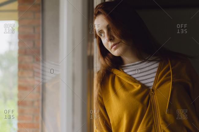 Portrait of redheaded woman looking out of window