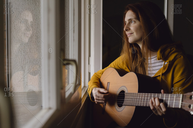 Portrait of relaxed redheaded woman playing guitar at open window
