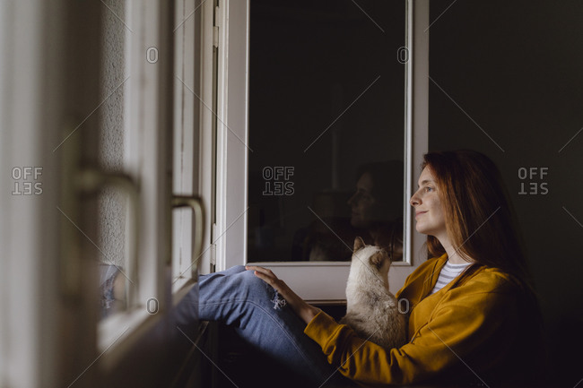 Smiling redheaded woman sitting at open window with her cat looking at distance