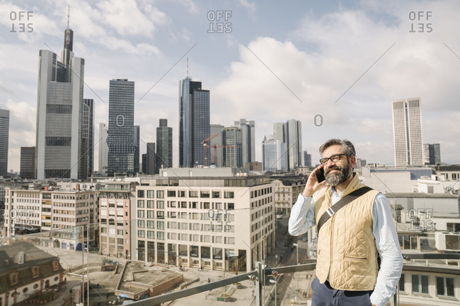 Man on the phone on observation terrace in front of skyscrapers- Frankfurt- Germany