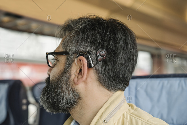 Profile of a man with cochlear implant in a train