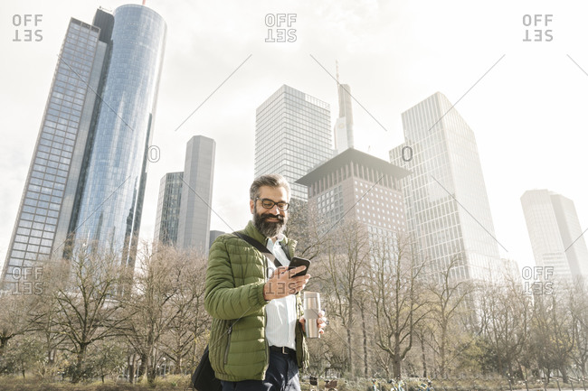 Man using smartphone in front of skyscrapers- Frankfurt- Germany