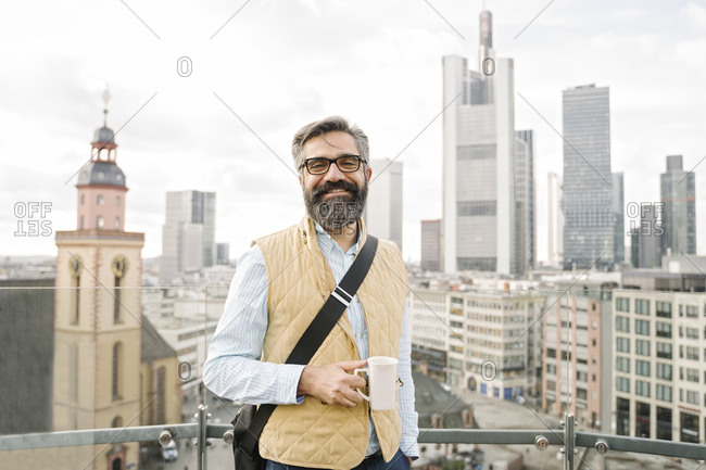 Portrait of smiling man on observation terrace in front of skyscrapers- Frankfurt- Germany