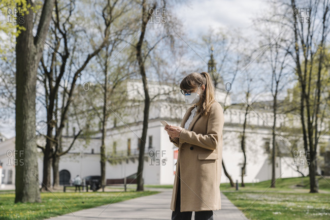 Woman wearing FFP2 mask and using smartphone in a park