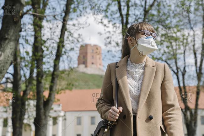 Woman wearing FFP2 mask looking sideways in the city