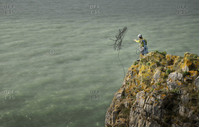 Rock climber throwing rope onto sea from cliff
