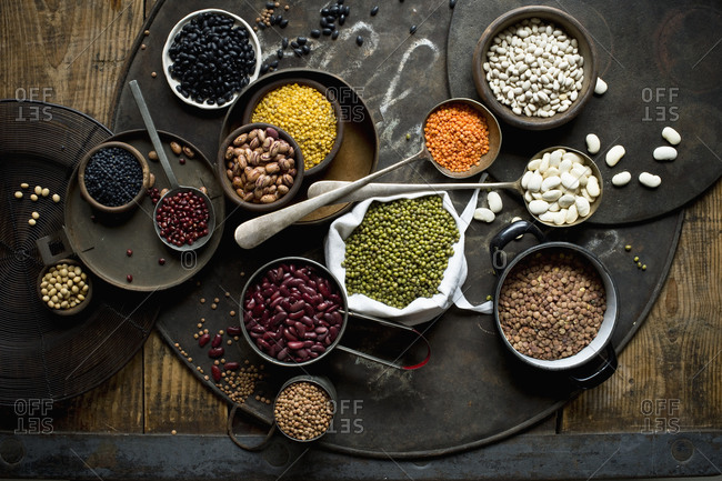Bowls with various beans and lentils on rustic baking sheet