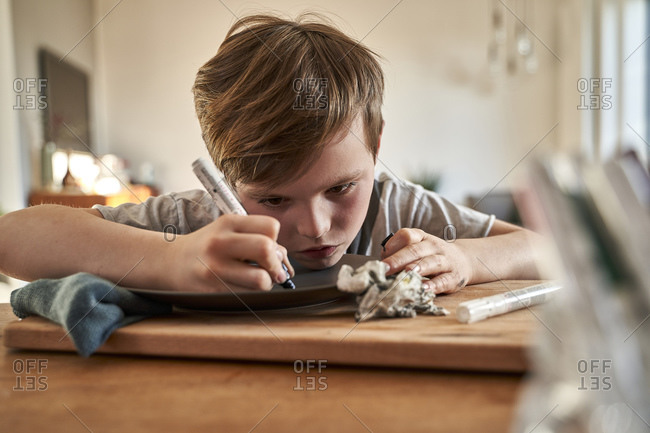 Focused boy at home painting plate with porcelain paint