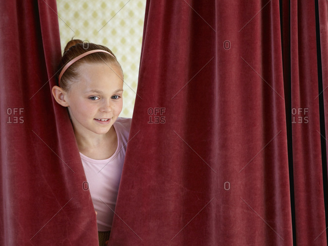 Portrait of smiling girl behind curtain