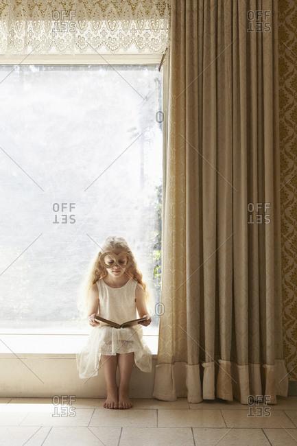 Girl sitting on windowsill wearing cardboard glasses reading book