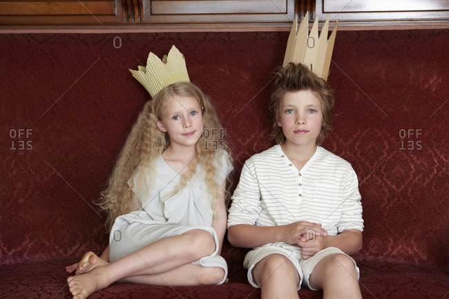 Boy and girl sitting on a couch wearing cardboard crowns
