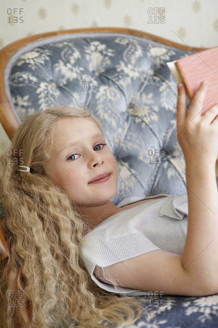 Portrait of a girl lying on a couch reading a book