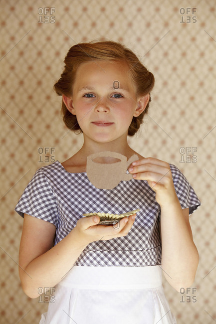 Portrait of a girl wearing apron playing with cardboard cup