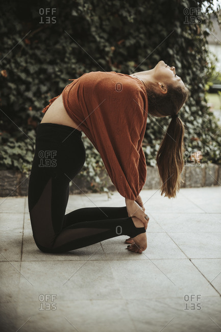 Woman practicing yoga in front of wall with ivy- camel pose