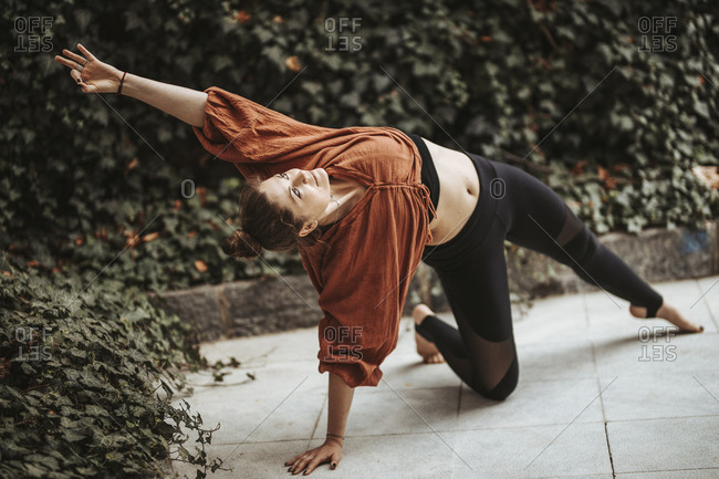 Woman practicing yoga in front of wall with ivy