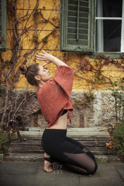 Woman practicing yoga in front of wall