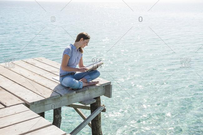 Woman sitting on jetty reading magazine- Mallorca- Spain
