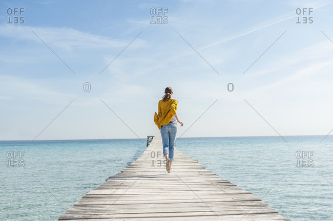 Back view of woman running barefoot on jetty- Mallorca- Spain