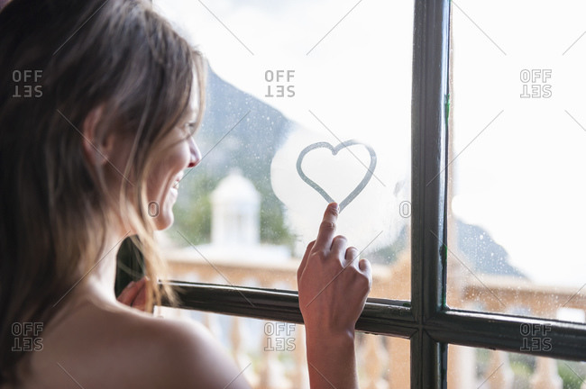 Happy woman drawing heart with her finger on fogges windowpane- Mallorca- Spain