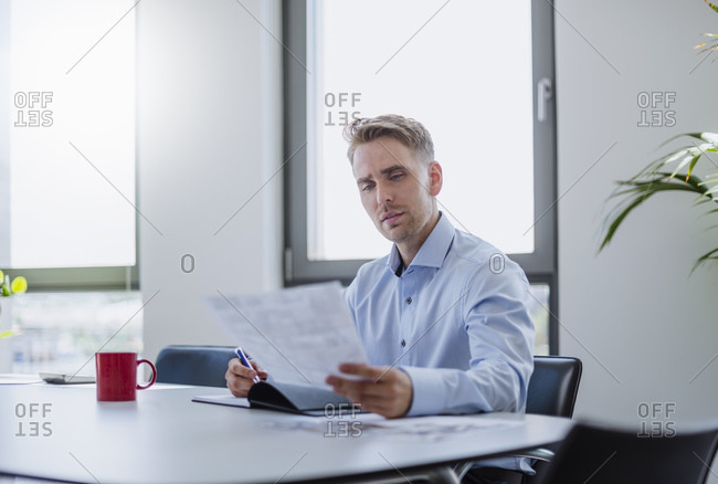 Businessman sitting at table in conference room reading papers