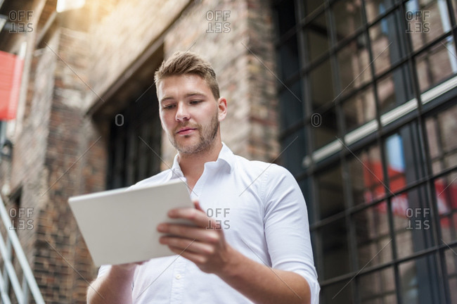 Young businessman using tablet at a brick building