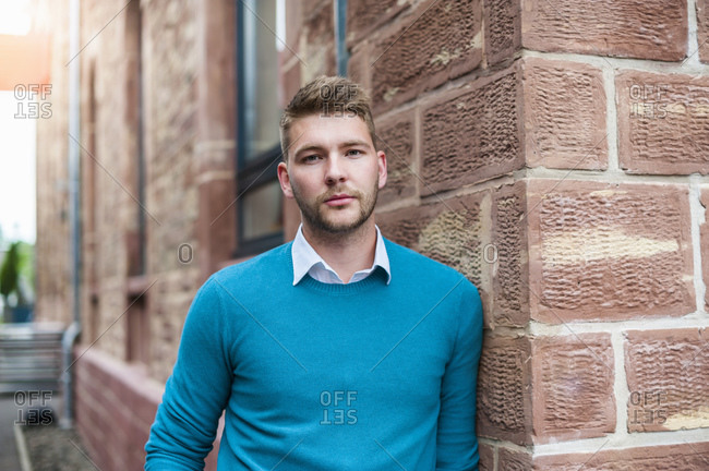 Portrait of a young businessman leaning against a brick building