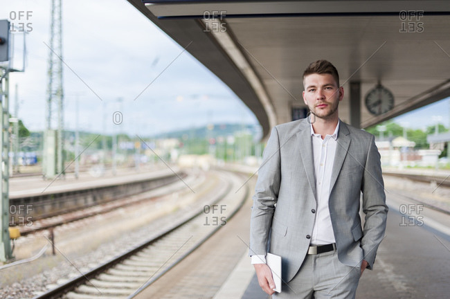 Portrait of young businessman on station platform