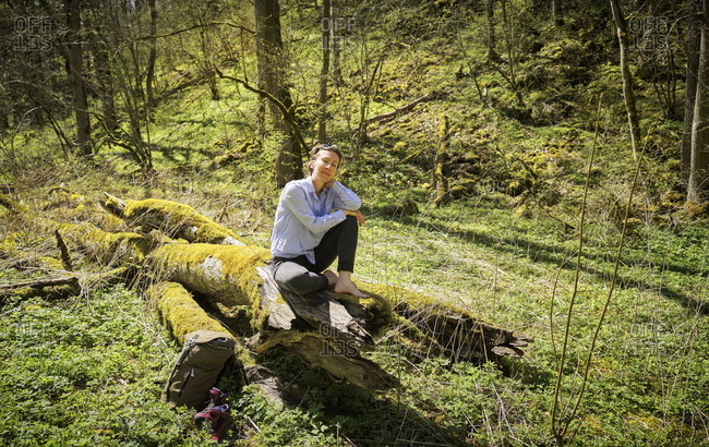 Full length of relaxed woman sitting on moss covered log in Swabian Jura forest