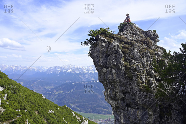 Female hiker sitting on rocky mountain peak while looking at landscape against sky